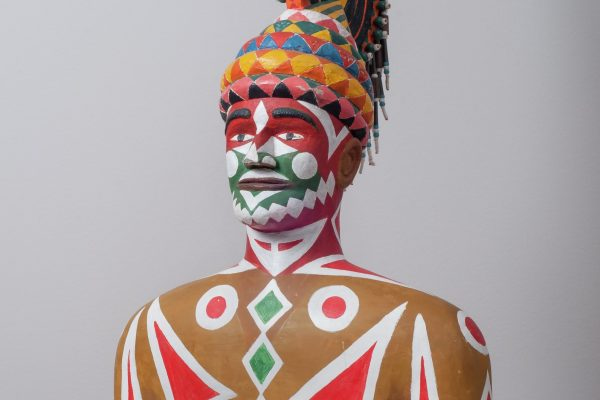 Painted figure by Eddie Owens Martin of a Pasaquoyan man covered in painted patterns and wearing a headdress
